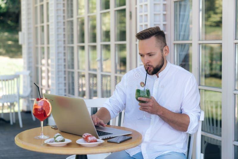 Бизнесмен работает на его компьтер-книжке, ждать его партнеров на таблице в кафе, выпивая холодный коктеиль стоковое фото rf