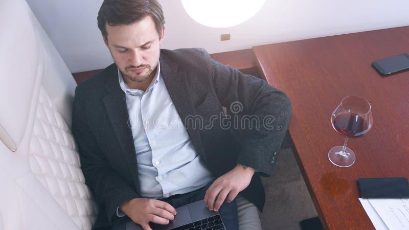Бизнесмен работает на частном самолете стоковые фото