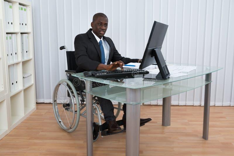 Бизнесмен работая в офисе сидя на кресло-коляске стоковая фотография rf