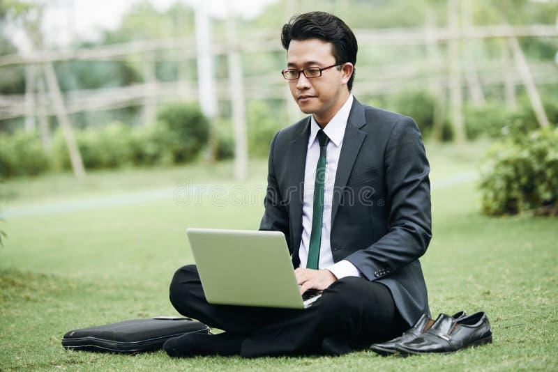 Бизнесмен работая в парке стоковые изображения rf