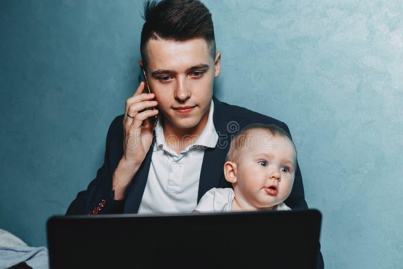 Бизнесмен работая дома наблюдая дочь младенца стоковая фотография rf