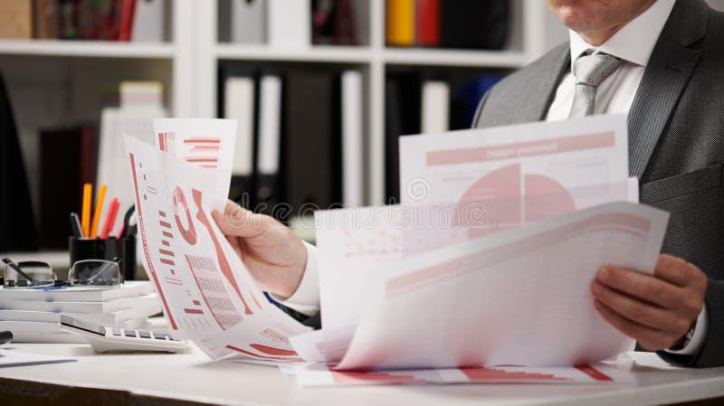 Бизнесмен работая и высчитывая, читает и пишет отчеты Работник офиса, крупный план таблицы Финансовый учет дела стоковые изображения