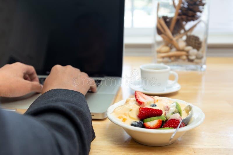 Бизнесмен работая на компьтер-книжке и имея шар югурта с фруктовым салатом и кофе стоковое изображение rf
