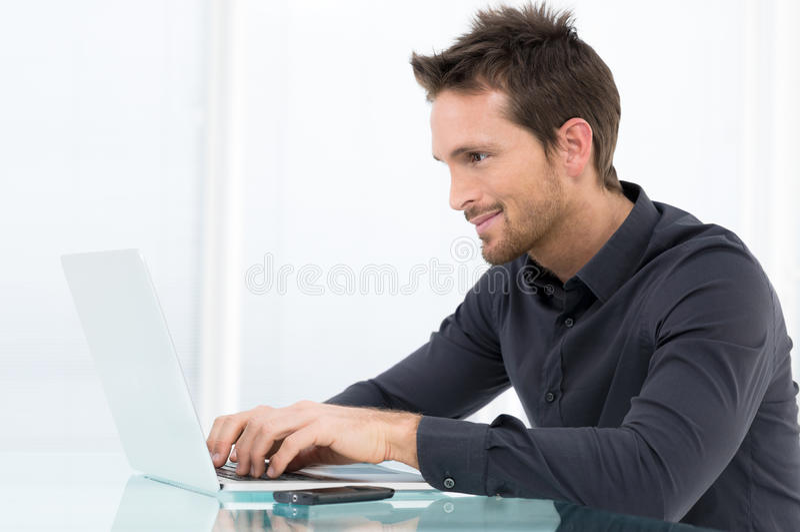 Бизнесмен работая на компьтер-книжке стоковое фото