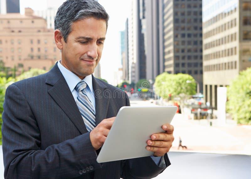Бизнесмен работая на компьютере таблетки вне офиса стоковая фотография rf