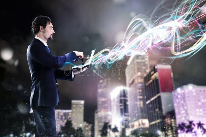 Бизнесмен работая на ноутбуке с новыми соединениями стоковая фотография