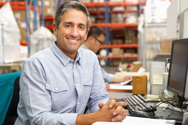 Бизнесмен работая на столе в пакгаузе стоковая фотография