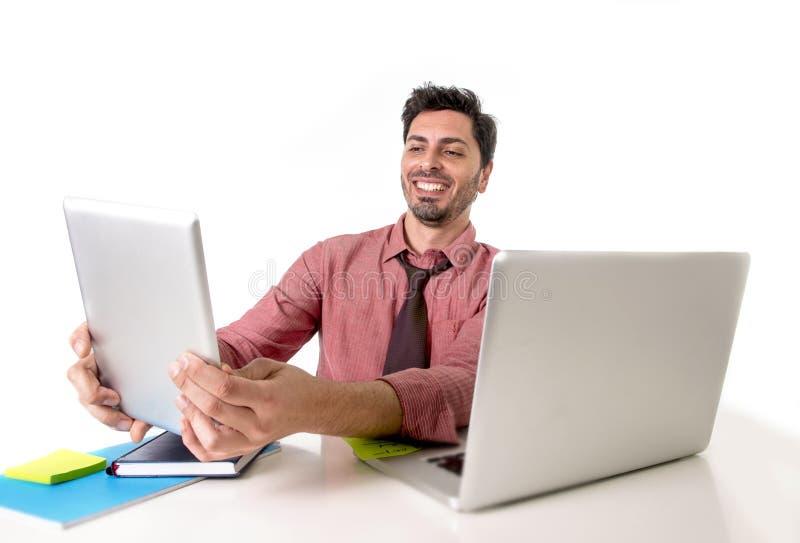 Бизнесмен работая на столе офиса используя усаживание цифровой пусковой площадки таблетки усмехаясь счастливое перед компьтер-кни стоковые фотографии rf