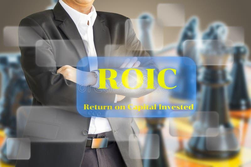 Бизнесмен рассматривая ROIC, возвращение на проинвестированное capit стоковая фотография