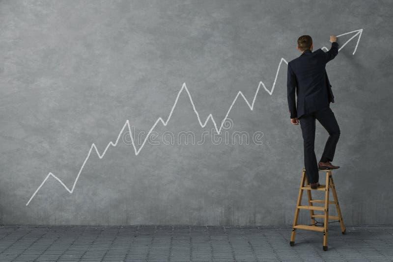 Бизнесмен рисуя финансовую диаграмму стоковое фото rf