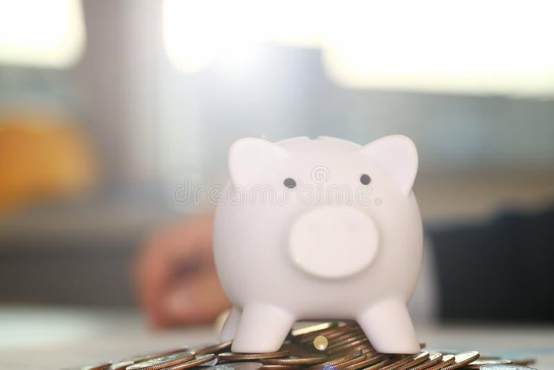 Бизнесмен руки кладя деньги штыря в свинью стоковое изображение