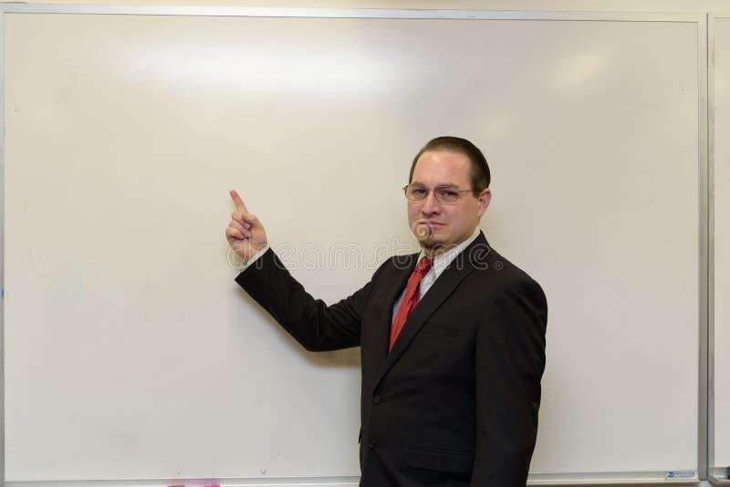 Бизнесмен рядом с белой доской стоковое фото