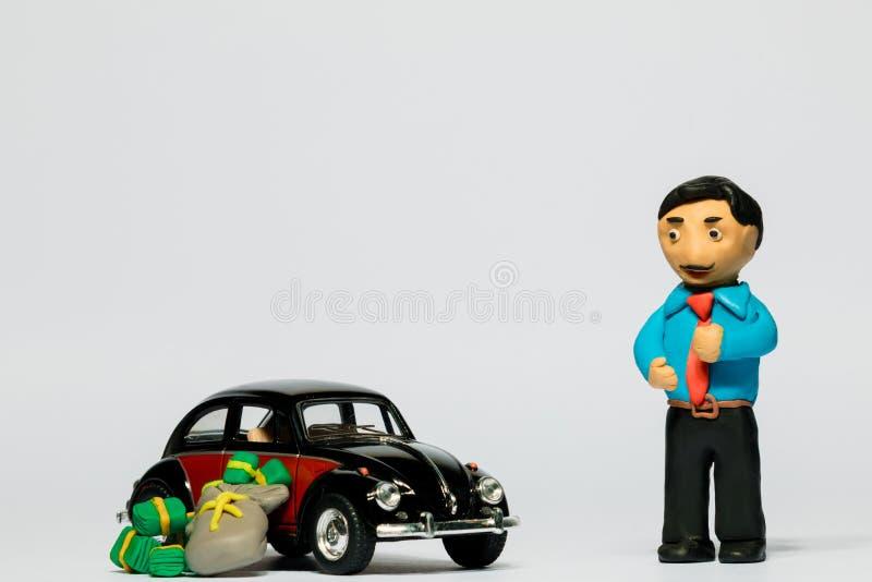 Бизнесмен сделанный из пластилина рядом с автомобилем и куча денег на белой предпосылке стоковые фотографии rf