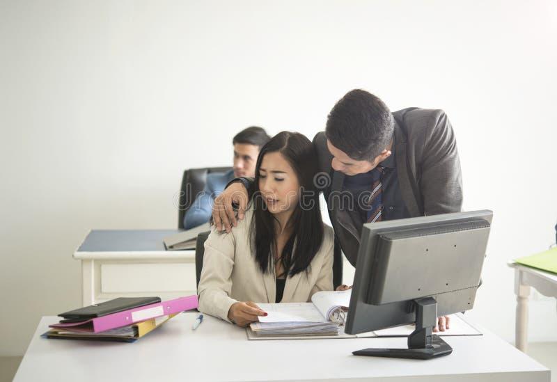 Бизнесмен сексуально изводя коллеги коммерсантки в офисе стоковая фотография