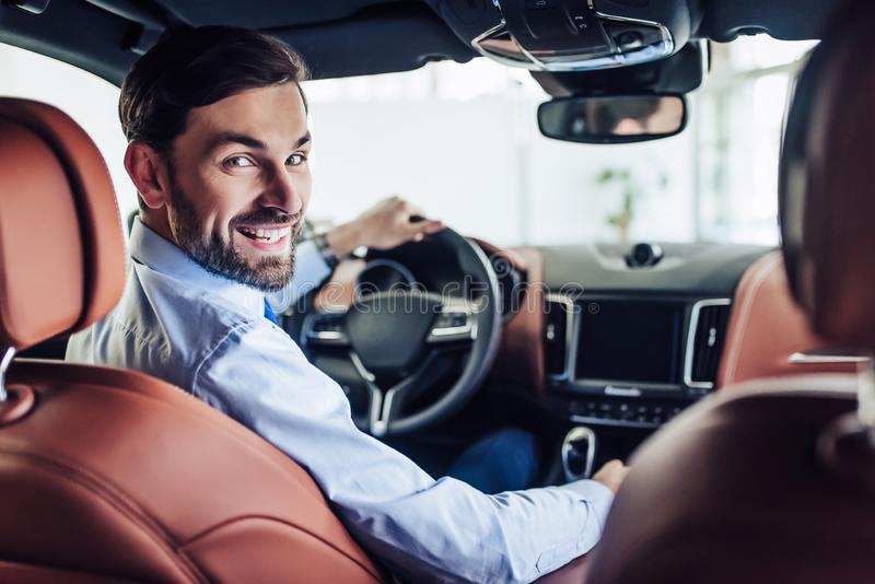 Бизнесмен сидя в автомобиле стоковое фото