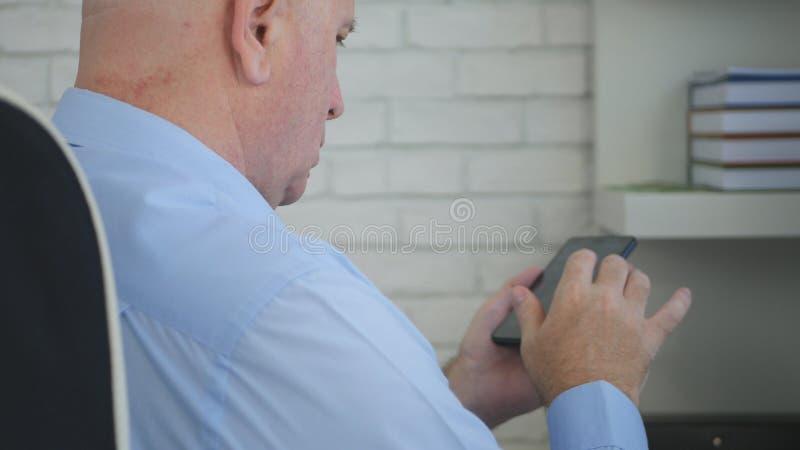 Бизнесмен сидя в тексте стула менеджера используя смартфон стоковая фотография