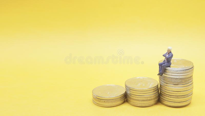 Бизнесмен сидя на куче серебряных монет стоковые фото