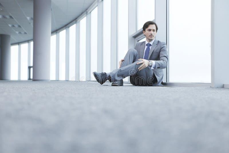 Бизнесмен сидя на поле стоковое фото