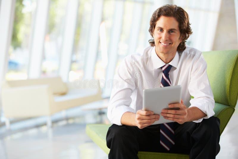Бизнесмен сидя на софе в офисе используя таблетку цифров стоковая фотография rf