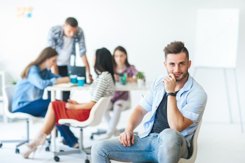 Бизнесмен сидя на стуле перед его командой дела стоковое фото