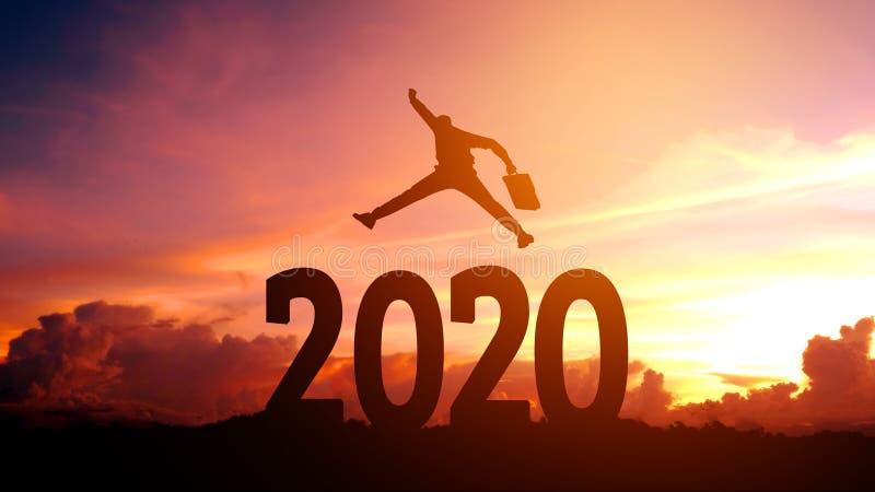 Бизнесмен силуэта молодой счастливый к концепции успеха 2020 Новых Годов стоковая фотография rf