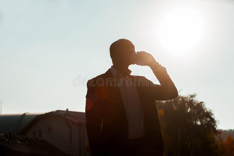 Бизнесмен силуэта с идти мобильного телефона стоковые фото