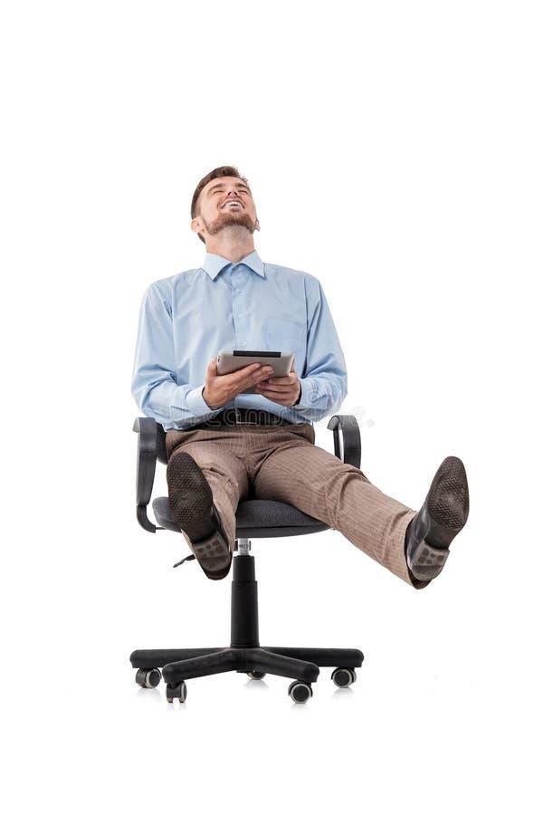 Бизнесмен сидя в стуле и используя таблетку стоковое фото rf