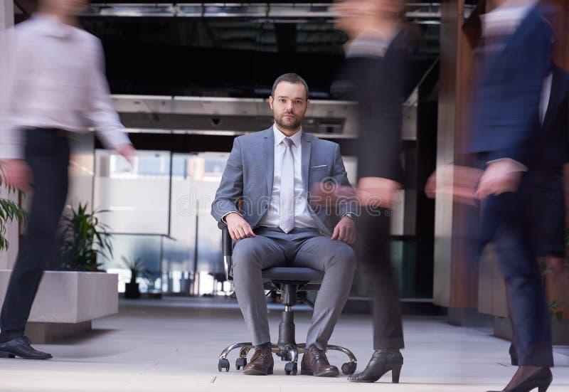 Бизнесмен сидя в стуле офиса, люди собирает проходить мимо стоковое фото