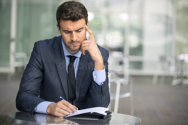Бизнесмен сидя на кофейне с обработкой документов стоковые изображения