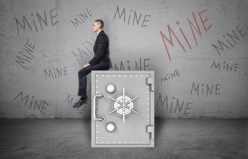 Бизнесмен сидя на сейфе и предпосылка стены с ` надписи минируют ` стоковая фотография