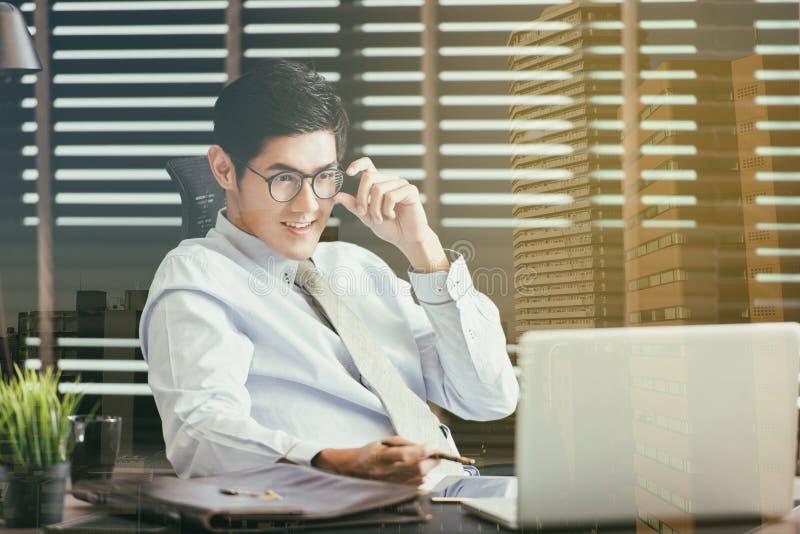 Бизнесмен сидя на столе офиса с портативным компьютером стоковая фотография
