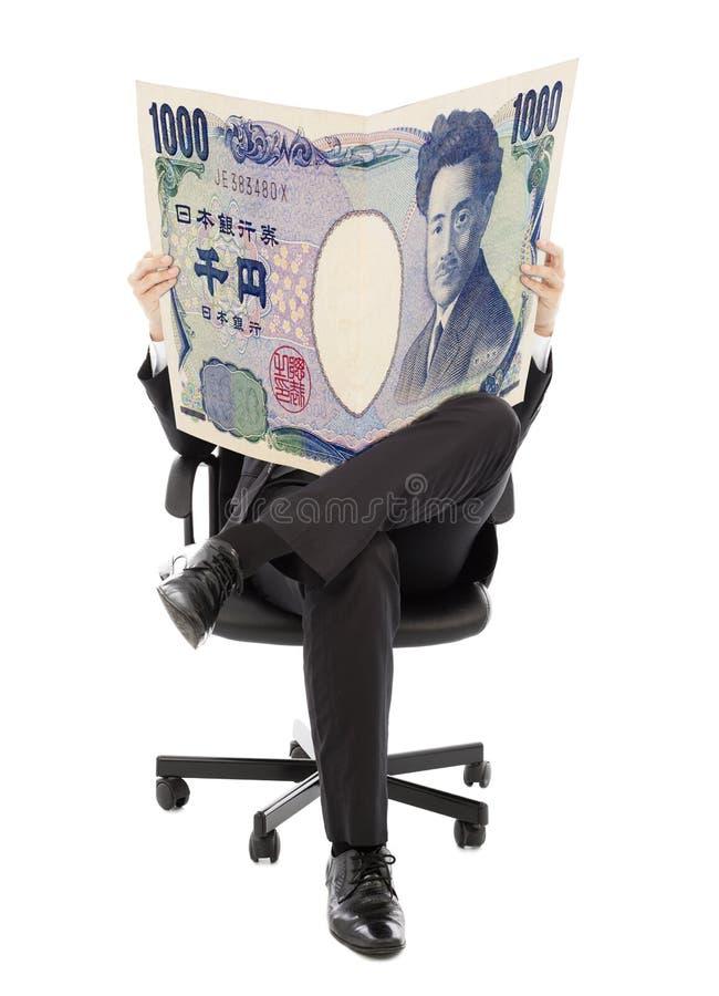 Бизнесмен сидя на стуле с деньгами на руках Японии стоковые изображения
