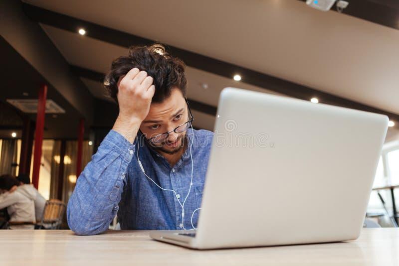 Бизнесмен сидя на таблице с портативным компьютером стоковое фото rf