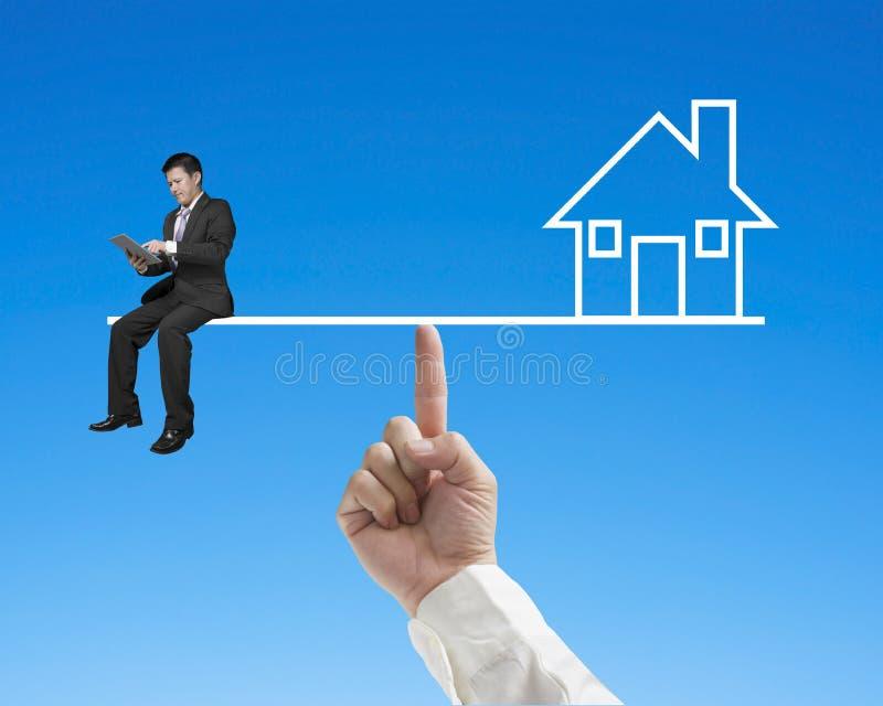 Бизнесмен сидя на seesaw с домашним балансом указательным пальцем стоковая фотография