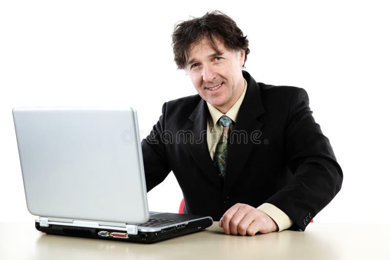 Бизнесмен сидя перед его компьютером и работой стоковые изображения