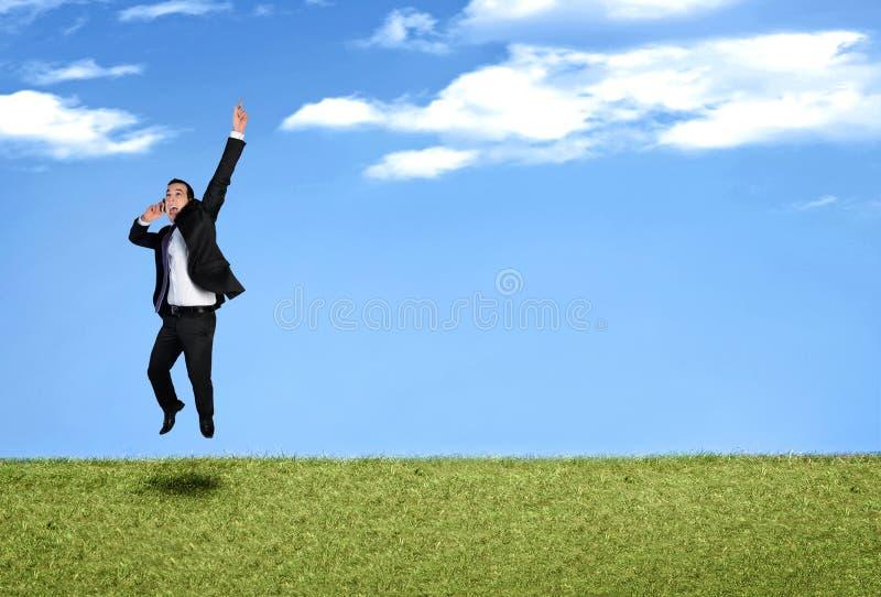 Бизнесмен скача в ландшафт стоковые изображения