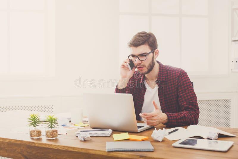 Бизнесмен сконцентрированный детенышами прочитал документы в современном белом офисе стоковые фото