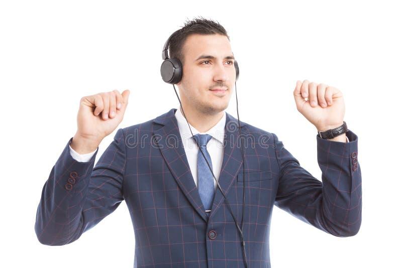 Бизнесмен слушая к музыке и танцевать стоковое фото