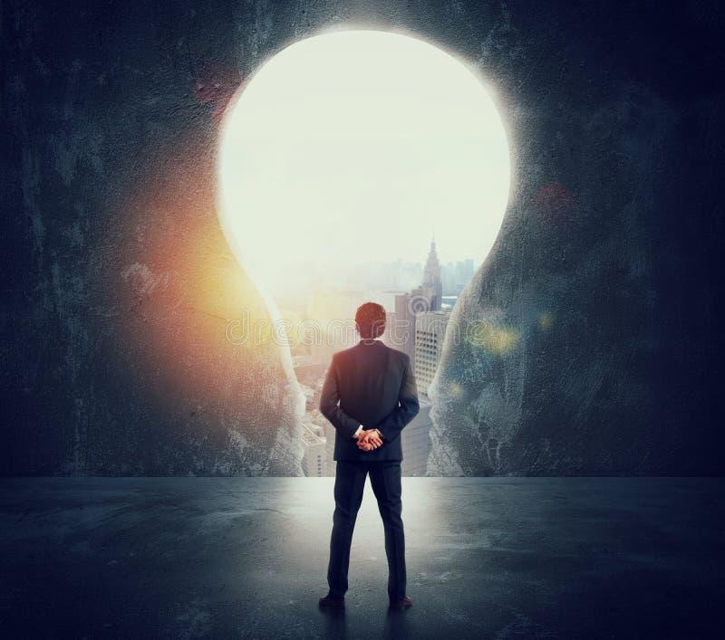 Бизнесмен смотрит большое отверстие на стене сформированной как электрическая лампочка стоковое изображение