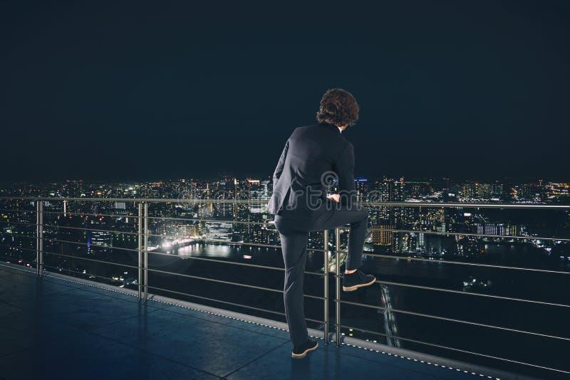 Бизнесмен смотрит город во время ночи Будущая и новая концепция возможности для бизнеса стоковое изображение rf