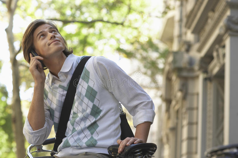 Бизнесмен смотря вверх пока отвечающ телефонному звонку на велосипеде стоковое изображение