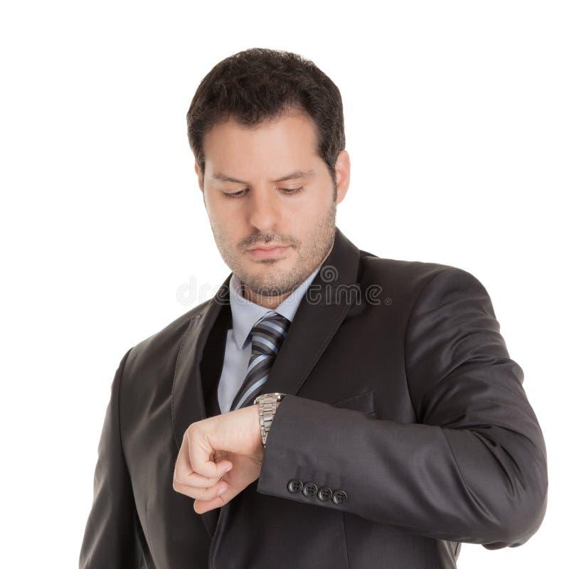 Бизнесмен смотря его дозор изолированный на белой предпосылке Дело, время концепция пунктуальности стоковое изображение rf