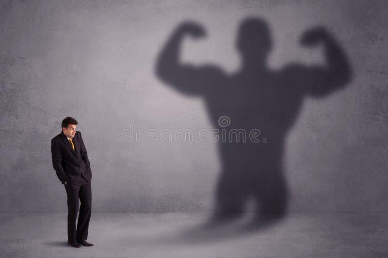 Бизнесмен смотря его собственную сильную концепцию тени пригонки стоковые фото