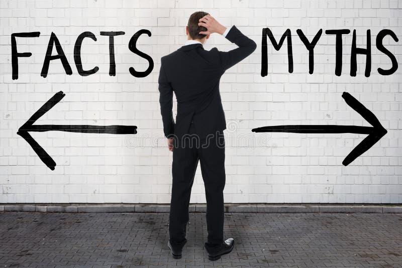 Бизнесмен смотря знаки стрелки под фактами и мифами стоковое изображение
