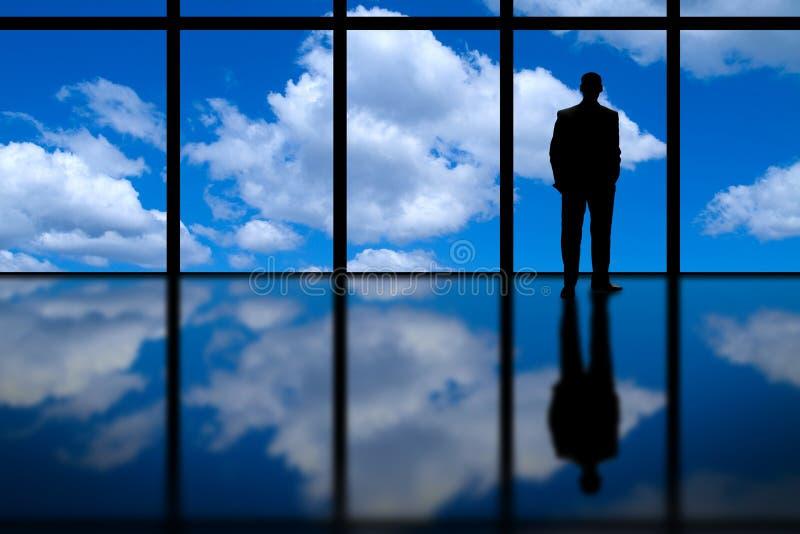 Бизнесмен смотря из высокого окна офиса подъема на голубом небе и облаках