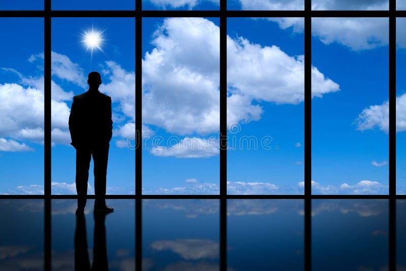 Бизнесмен смотря из высокого окна офиса подъема на ярком свете голубого неба и белых облаках.