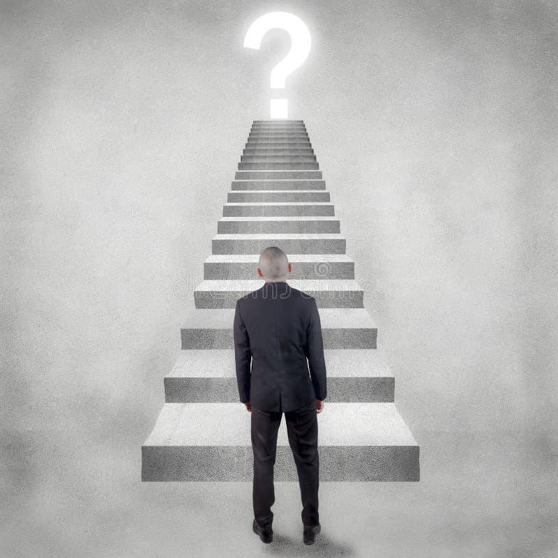 Бизнесмен смотря на вопросительный знак над верхней частью лестницы стоковые фотографии rf
