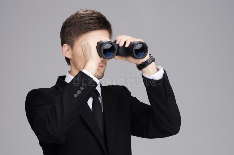 Бизнесмен смотря до бинокли стоковое фото