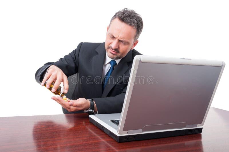 Бизнесмен смотря усиленный принимающ пилюльки стоковая фотография
