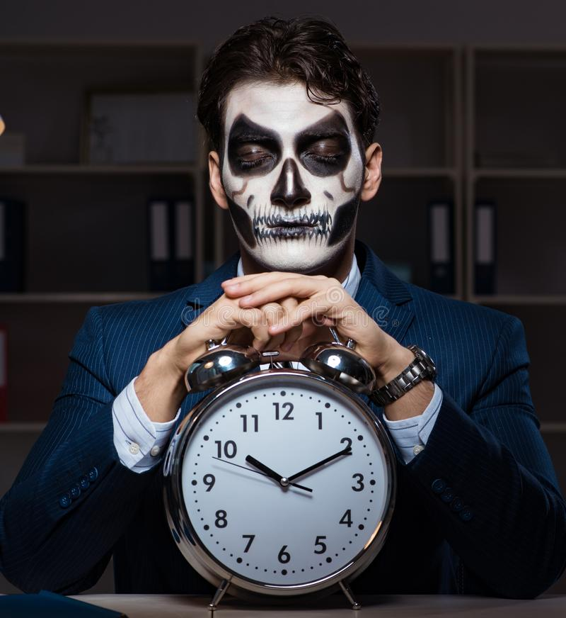 Бизнесмен со страшной деятельностью лицевого щитка гермошлема поздно в офисе стоковое изображение rf